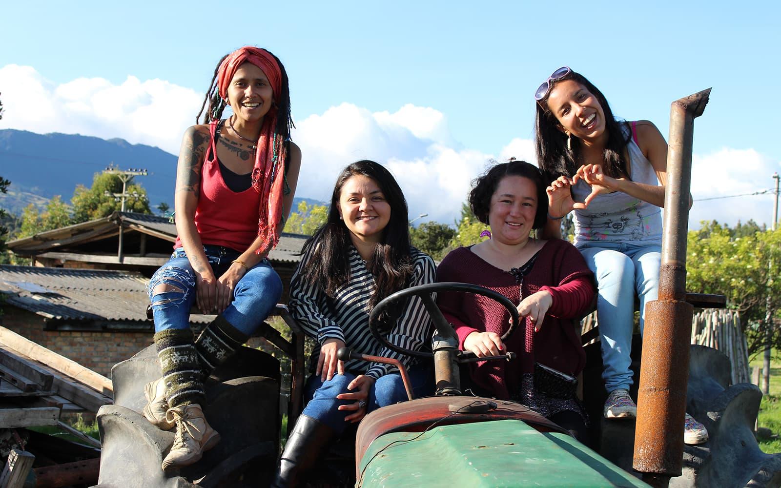 4 jeunes femmes du Honduras et participant à l'un de nos projets assises sur un tracteur