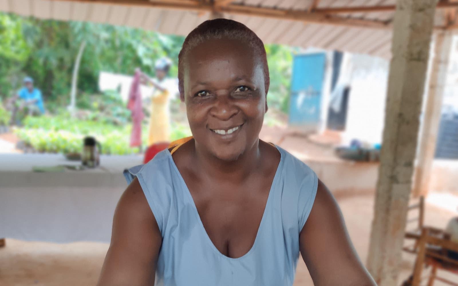 Une femme haïtienne qui montre avec fierté ses récoltes dans le cadre du projet Kafé Makaya
