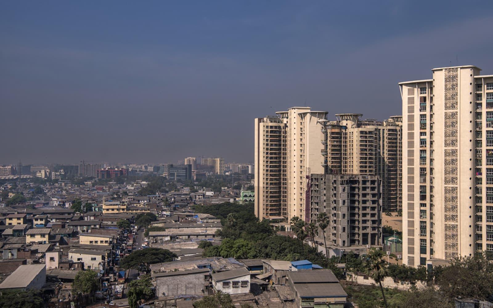 Une photo montrant des tours d'habitation luxueuses bordant un bidonville
