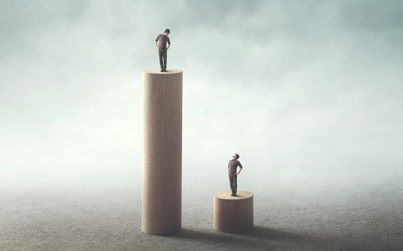 Deux personnes se tiennent du des colonnes de grandeurs différentes afin d'illustrer les inégalités.