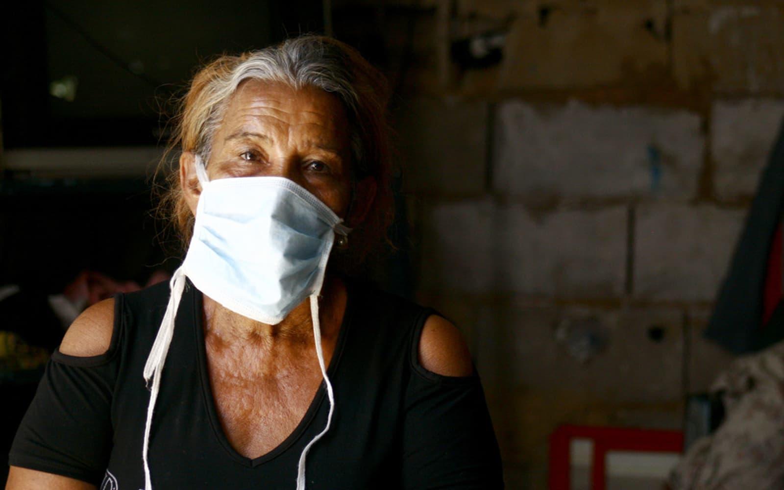 Une femme Vénézuélienne âgée portant un masque