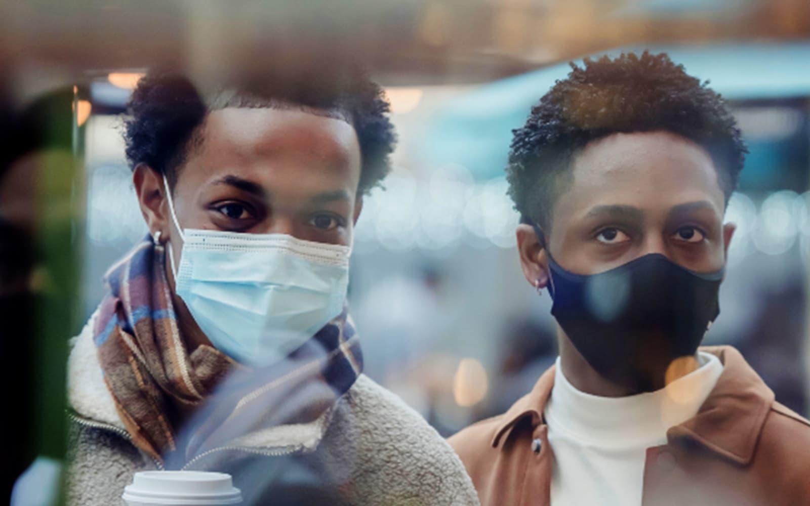 Deux jeunes hommes masqués qui regardent par une fenêtre.