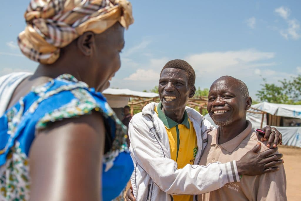 Photo montrant un réfugié qui rencontre un vieil ami sur le marché du camp des réfugiés en Ouganda.