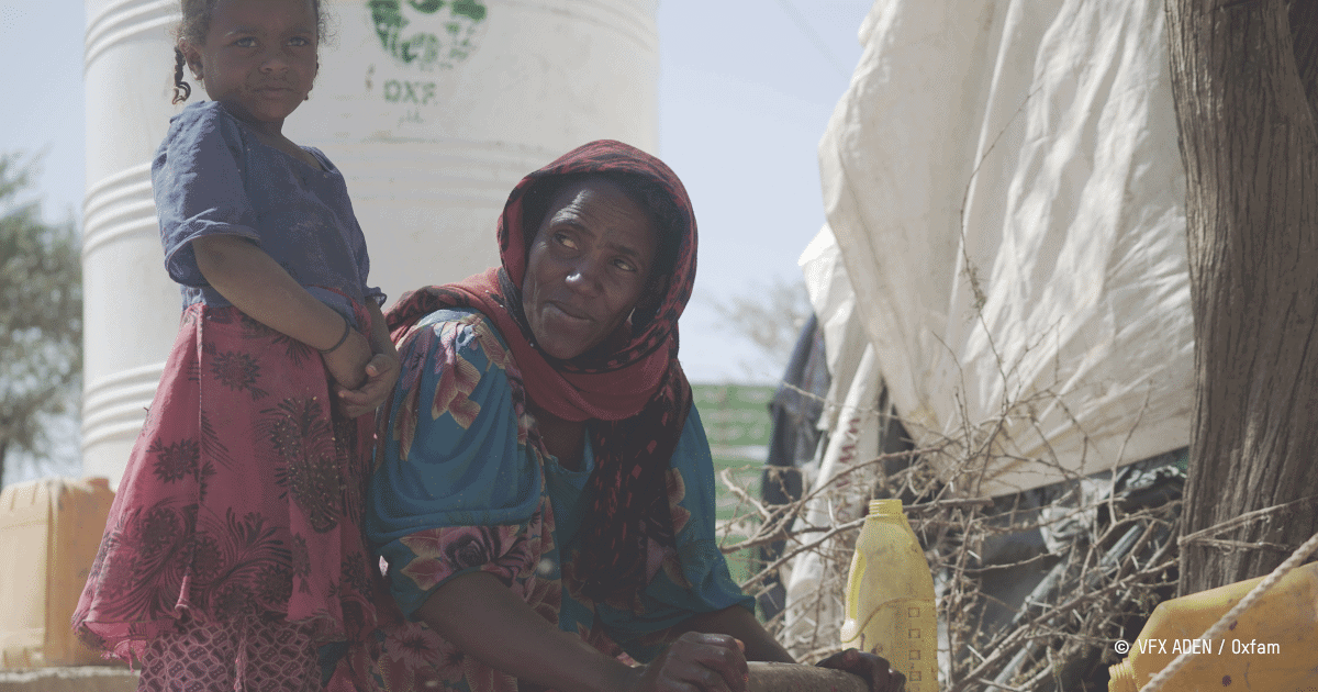 une femme yéménite prépare un repas en compagnie d'une enfant dans un camp de personnes réfugiées